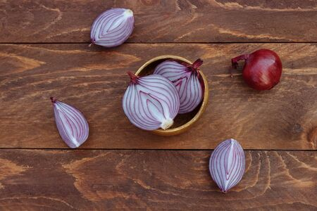 Red onions whole and cut in halves and quarters in a bowl on a brown wooden background top view Фото со стока