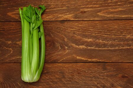 A bunch of green celery stalks close up on a brown wooden background top view with free space for text