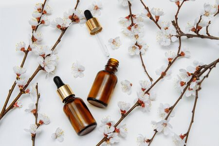 brown glass cosmetic bottles with pipette on a white background with cherry blossoms on the branches