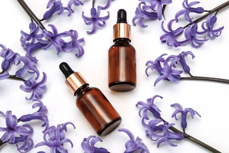 Brown, glass, cosmetic bottles with pipette on a white background with lilac hyacinth flowers top view