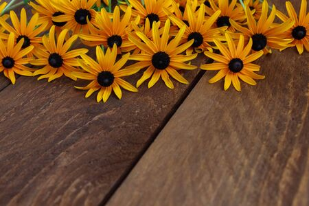 A bouquet of yellow daisies with a black center for congratulations lies on a brown wooden table with an empty space for text Stock Photo