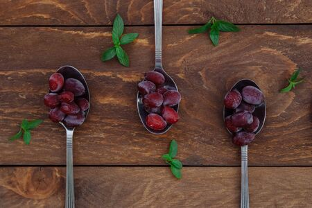 Red ripe frozen dogwood berries lie in tablespoons with green mint leaves on a brown wooden background view from the top
