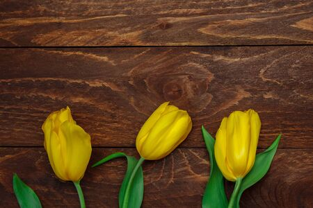 A bouquet of yellow tulips with green leaves on a brown wooden background with free space for text top view