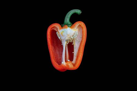 Half red pepper, paprika with seeds and green peduncle isolated on a black background, top view