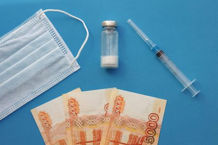 Disposable medical mask with a bottle of medicine, a syringe and paper banknotes of Russian rubles view from the top
