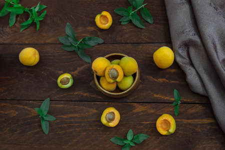 Ripe, juicy, sweet yellow apricots in a bowl whole and cut with a stone and green sprigs and mint leaves and a napkin on a brown wooden table top view, concept pie filling and jam ingredients
