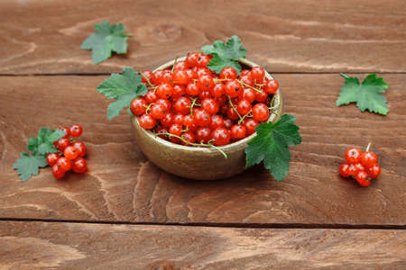 Berries of ripe, red and juicy currants in a wooden bowl with green leaves on a brown wooden table close-up, the concept of vitamin berries and pie filling