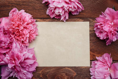 Pink peony flower frame with paper vintage blank greeting card and text on brown wooden background top view, flat composition, greeting card concept, cover
