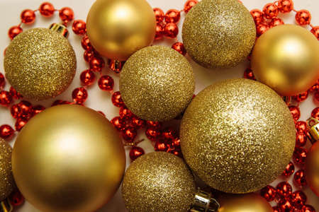Gold Christmas balls of different sizes matt and shine with red beads, garlands on a white background close-up, new year celebration concept, greeting card, decoration, design and template