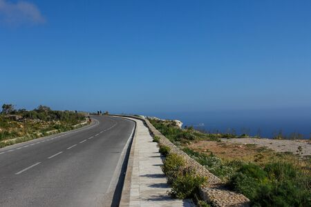 The road goes into the horizon against a clear blue sky and sea.