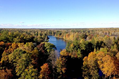 Panoramic top view of the bend of the river and the colorful crowns of trees in the autumn in the sunlight. Skyline in the clouds Banco de Imagens
