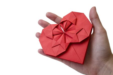 Isolated red paper heart made in origami technique in female hand on a white background with a shadow. Concept of love, celebration, care, health, life Banco de Imagens