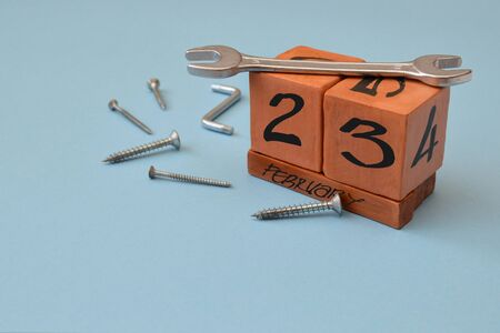Perpetual wooden calendar with the date of February 23, a wrench and self-tapping screws on a blue background with copy space. Concept of holiday, Defender of the Fatherland Day, courage, strength