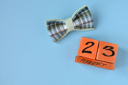 Perpetual wooden calendar with the date of February 23 and a bow tie on a blue background with copy space. Concept of Defender of the Fatherland Day, courage, strength. Horizontal photo