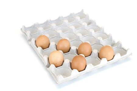 Isolated close-up of six brown chicken eggs lying in a cardboard tray on the diagonals. Easter concept