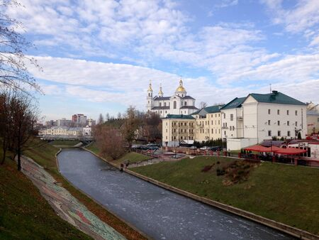 View of the church and the buildings behind the river, covered with ice, against the blue sky with clouds. Vitebsk, Belarus Imagens