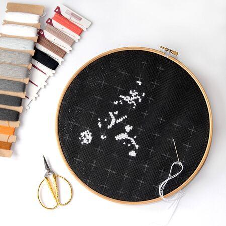 Beginn der Stickerei auf schwarzer Leinwand mit Wollfäden. Kreuzstich-Malerei mit Maine Coon Cat Standard-Bild