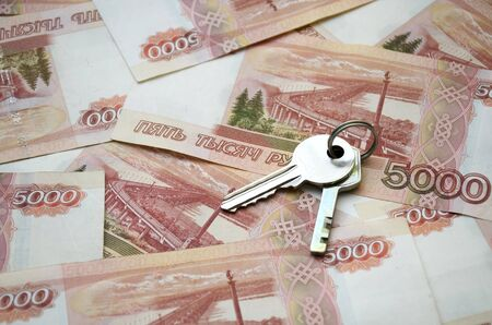 Metal keys on a horizontal background of a variety of banknotes of five thousand Russian rubles. Concept of buying an apartment, flat or house, mortgage, rental housing, housewarming, home expense