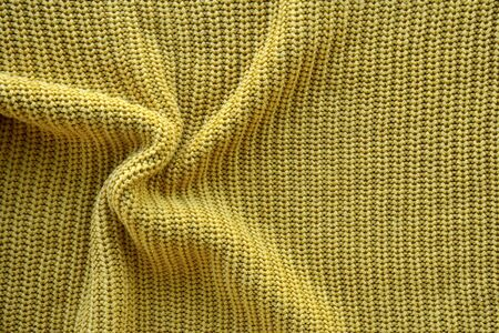Yellow texture of a knitted English elastic pattern. Horizontal background from a close-up of a knitted crumpled mustard-colored canvas with copy space. Textile concept