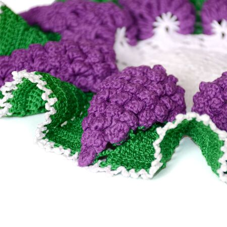 A part of isolated crocheted doily in shape of a violet grape with green leaves