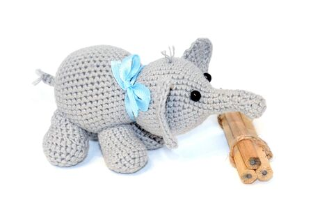 Isolated crochet amigurumi toy gray elephant with a blue bow on the neck and black beaded eyes stands next to a bunch of wooden pencils on a white background. Side view Фото со стока