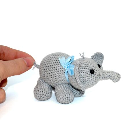 Isolated crochet amigurumi toy gray elephant with a blue bow on the neck and black beaded eyes on a white background. Female hand gently holds the elephant by the tail. Side view