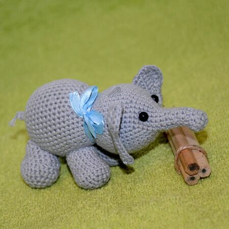 A crochet amigurumi toy gray elephant with a blue bow on the neck and black beaded eyes stands next to a bunch of wooden pencils on a green terry background. Side view