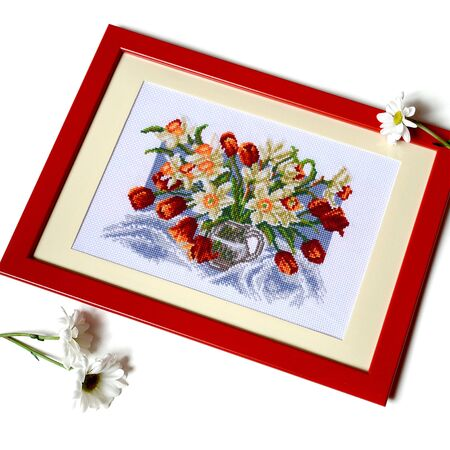 Cross stitched picture with tulips and daffodils in jug. Isolated embroidery with flowers in red frame surrounded by daisies Фото со стока