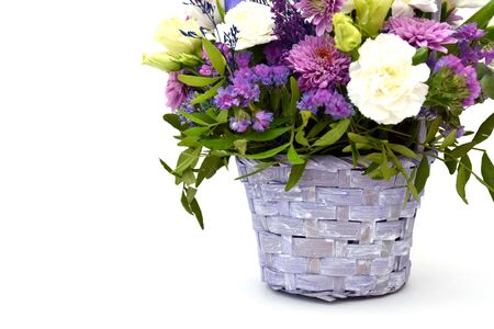 Isolated bouquet of spring flowers in wicker wooden basket of lilac and purple colors on white background. Concept of March 8, Womens Day. Iris, roses and asters with greenery in decorative flower pot Фото со стока