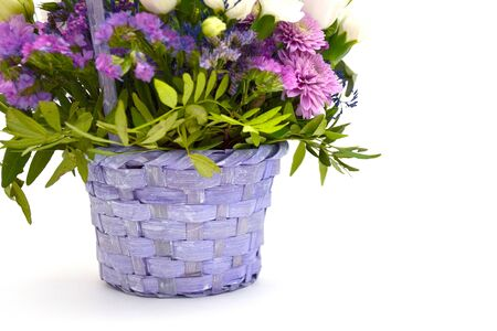 Isolated bouquet of spring flowers in wicker wooden basket of lilac and purple colors on white background. Concept of March 8, Womens Day. Iris, roses and asters with greenery in decorative flower pot Stock Photo - 129419362