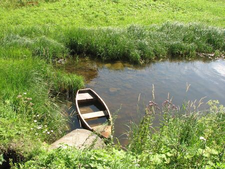 Old flooded wooden boat in a river creek near the coast, covered with grass, on a sunny summer day