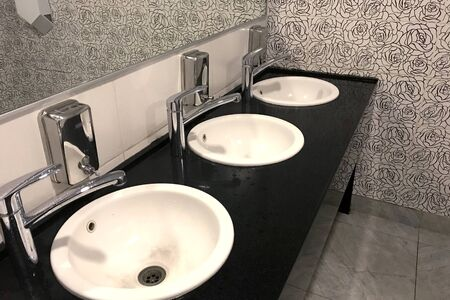 White sinks on the black tabletop in a public toilet. Shiny chromed faucets and dispensers for liquid soap, gray tile on the floor and a mirror. Side view