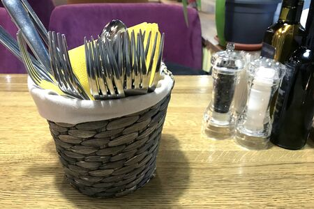 Wicker basket with cutlery and yellow napkins on wooden table in a restaurant. In background are purple chairs, saltcellar, pepper shaker, bottles of wine. Method of serving forks, spoons and knives