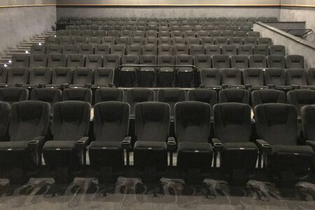 Bottom view of the way to the cinema hall with black soft chairs. Rows of chairs amphitheater in the interior