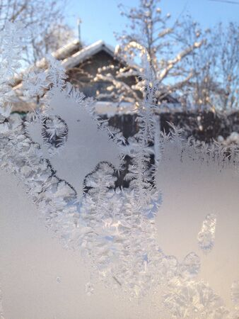 Ice pattern on winter window in a village on a sunny day. House on the background