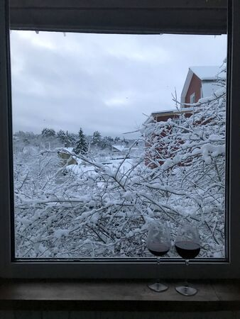 Two glasses of wine on the window overlooking the winter landscape