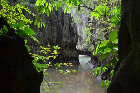 View from the darkness of the Ice cream cave on a mountain and lake among the greenery, Phang Nga province, Thailand. Photo framed by shadow and foliage of trees