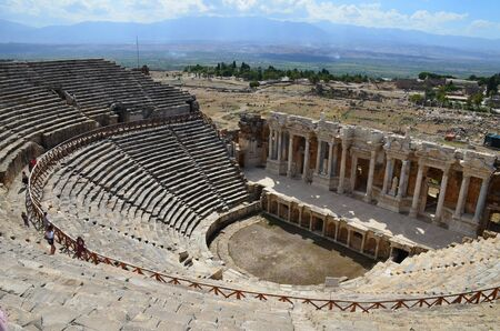 The ruins of the amphitheater of the ancient city of Hierapolis on the background of the mountains near Pamukkale, Turkey. People explore the sights under the bright summer sun