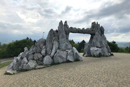 Gate of Love, Gate of the Sun. Symbolic construction of stones on the brick pavement against a background of green trees and sky with clouds in summer. Pyatigorsk, Russia Stock fotó