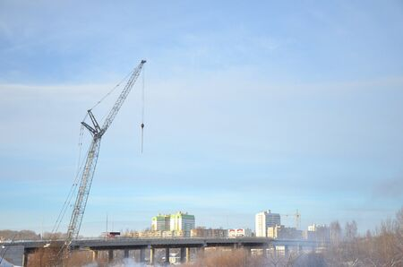 Gray tower crane towering over the bridge on the background of high-rise buildings and blue sky. The concept of construction, industry, work Banco de Imagens