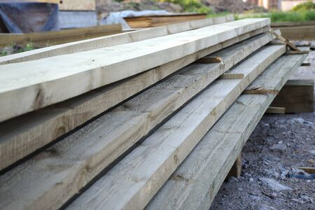 Close-up of a stack of long wooden boards. The concept of building wooden country houses