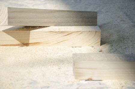 Background from smooth pine wood bars lying on a pile of sawdust and shavings in the rays of sunlight. Selective focus. The concept of carpentry, woodworking, handmade, male hobby