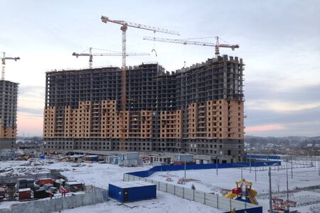 The process of building a large multi-storey residential building in the winter. The work of construction cranes. Half built house on the background of the morning sky. New house for many families.