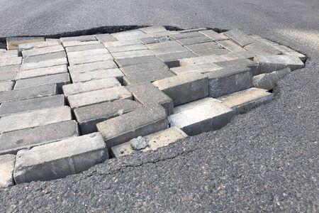 Road repair concept. Closeup of a pit with a brick in an asphalt road