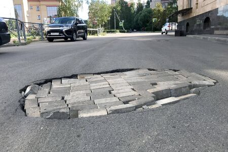 Road repair concept. Closeup of a pit with a brick in an asphalt road. In the background buildings and parked cars