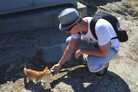 Caucasian man in a t-shirt, hat and sneakers with a backpack crouched down and holding an action camera in his outstretched hand. Red kitten sniffs the camera.