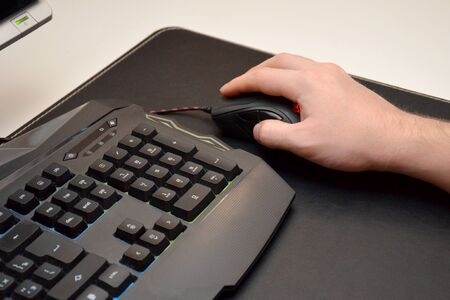 Guy is playing a video game. Close up of a hand lying on a laptop mouse and a black gaming keyboard with multi-colored backlight on a black table. Side view Banco de Imagens
