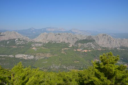 Panorama of the Taurus Mountains on the background of a summer blue sky on a sunny day near Antalya, Turkey. In the foreground are green trees, in the background are mountains in haze