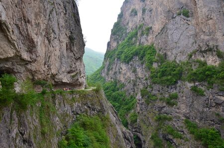 Cherek Gorge in Kabardino-Balkaria in the North Caucasus, Russia. Breathtaking view of the mountain gorge and a narrow path along steep cliff overgrown and trees. People walk over the precipice