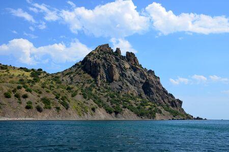 Kara dag Mountain towers over the Black Sea near the village of Koktebel, Crimea, Russia. Extinct volcano, view from the sea